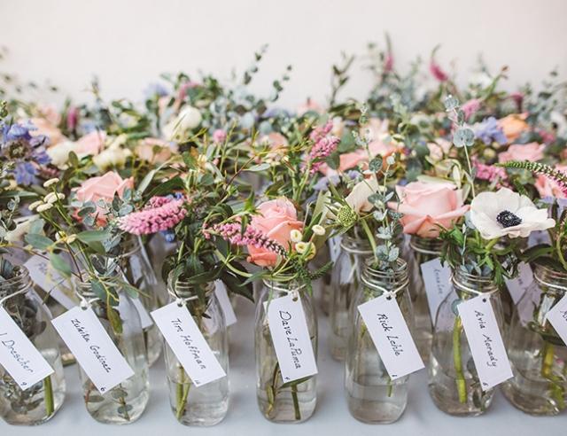 Miniaturní vázička s čerstvými květy, ke které připojíte papírovou jmenovku, potěší zaručeně každého svatebního hosta.